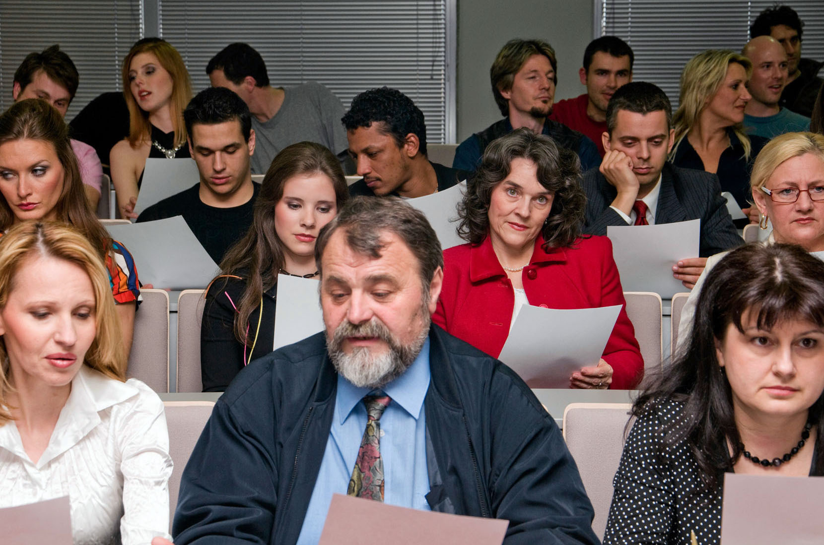 Adult Learners Seated in Classroom Reading Paper